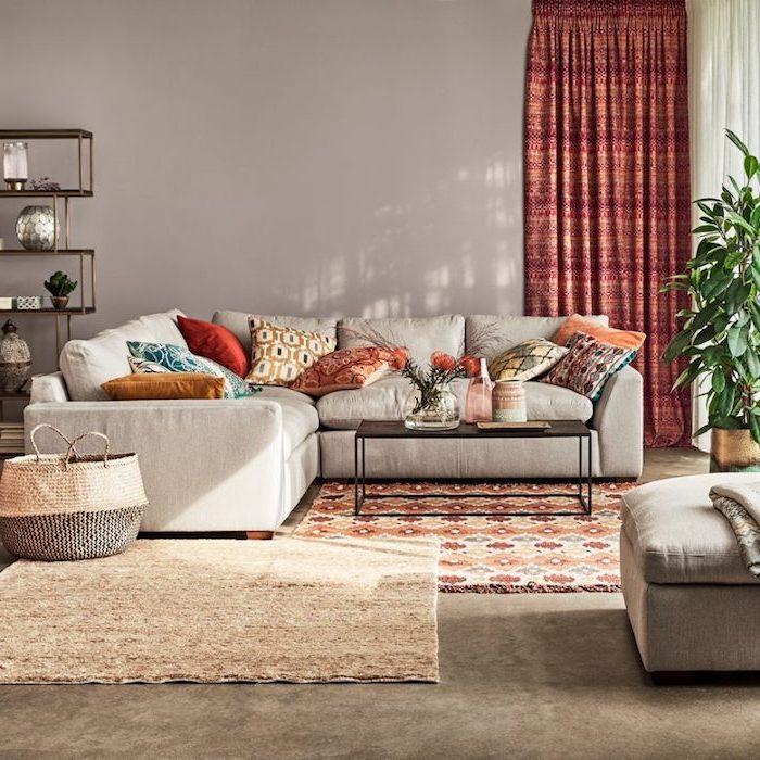 Wohnzimmer Einrichtung in Pastellfarben, bunte Deko Kissen, große Grünpflanze, weißes Sofa und schwarzer viereckiger Couchtisch