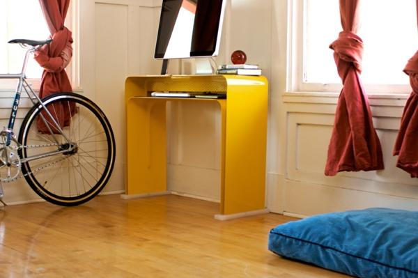 designerschreibtisch - kleines gelbes modell und ein fahrrad daneben
