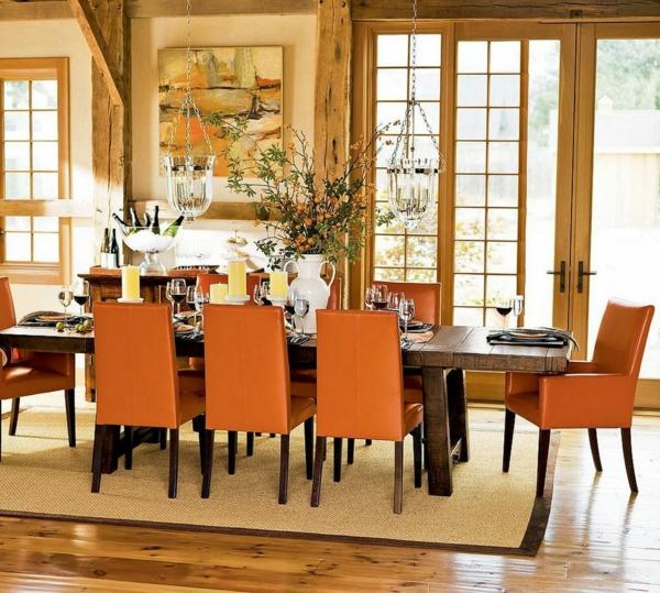 landhausdekoration -grüne pflanzen auf dem esstisch und orange stühle
