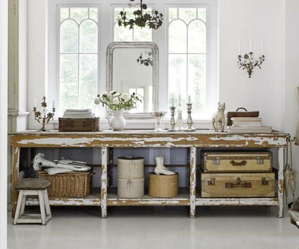 landhausdekoration -rustikaler spiegeltisch mit blumen und kerzen darauf