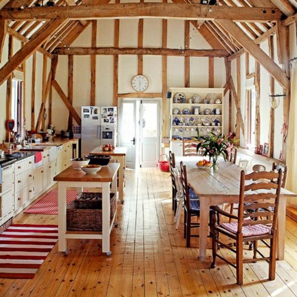 landhausdekoration - blumen auf dem hölzernen esstisch ganz neben der küche