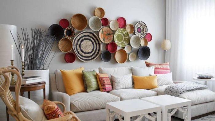 Wohnzimmer Deko Ideen, bunte Schüsseln an weißer Wand, farbenfrohe Deko Kissen, weißes Sofa, weißer viereckiger Holztisch