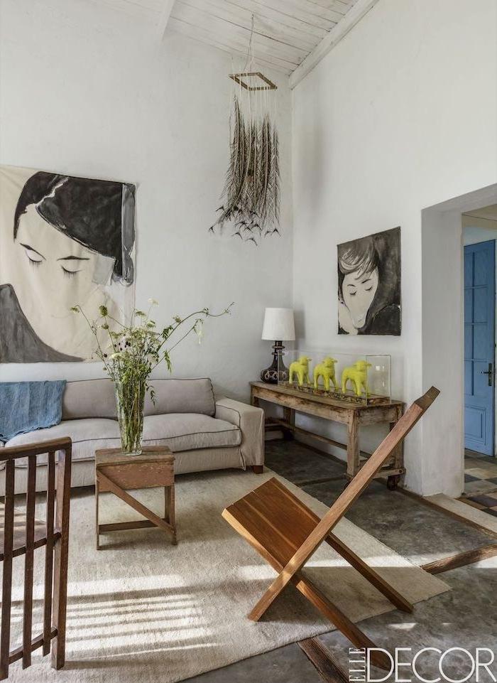 Moderne Wohnzimmer Dekoration, zwei Frauengesicht Gemälde, drei hellgrüne Lamm Figuren, Feldblumen in Glasvase
