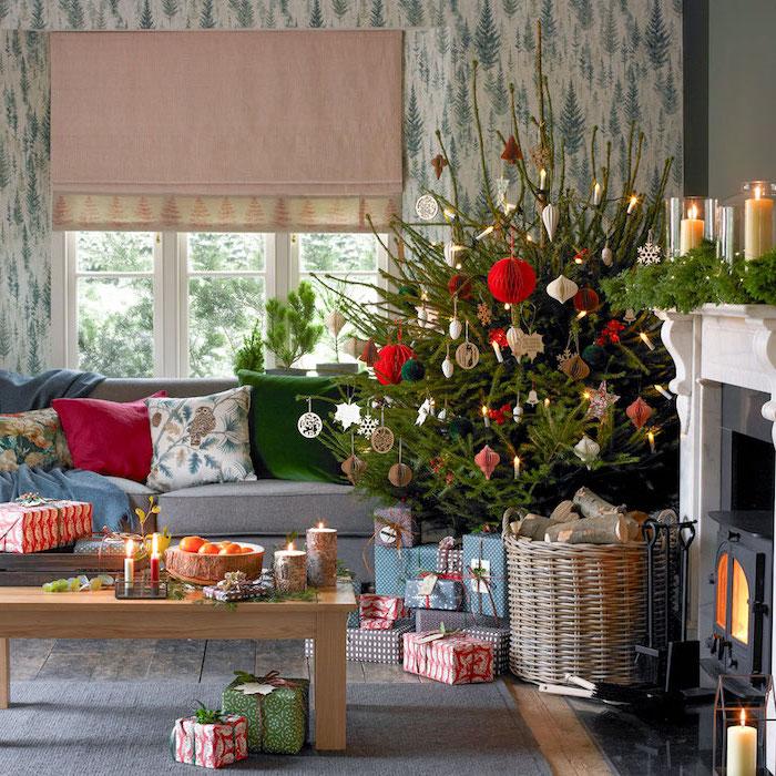 Weihnachtsdekoration in Wohnzimmer, echter Tannenbaum, Weihnachtsschmuck aus Papier und Holz, Weihnachtsgeschenke in bunten Verpackungen, graues Sofa mit bunten Kissen