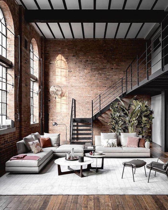Wohnzimmer Einrichtung in Industrial Stil, nackte Wände, weiße Sofas, runder Couchtisch zweiteilig, Treppe aus Metall