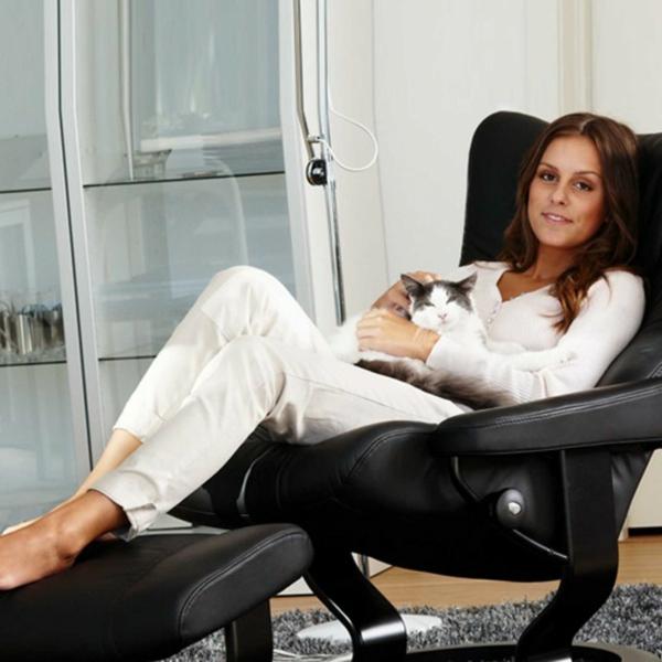 eine-frau-in-weiß-angekleidet-erholt-sich-in-einem-stressless-sessel-in-schwarzer-farbe