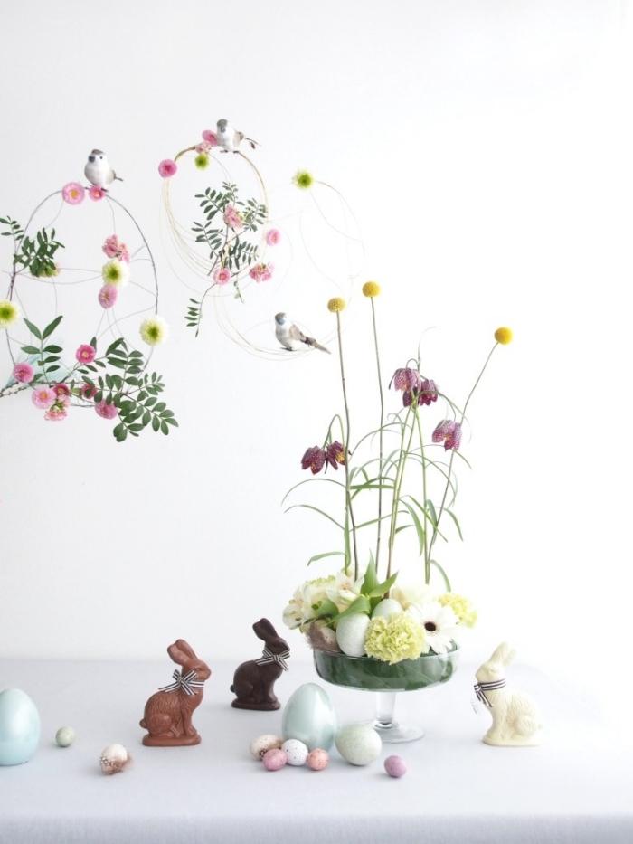 frühling deko tisch gesteck,osterdeko in weiß, glasvase dekroiert mit eiern und blumen