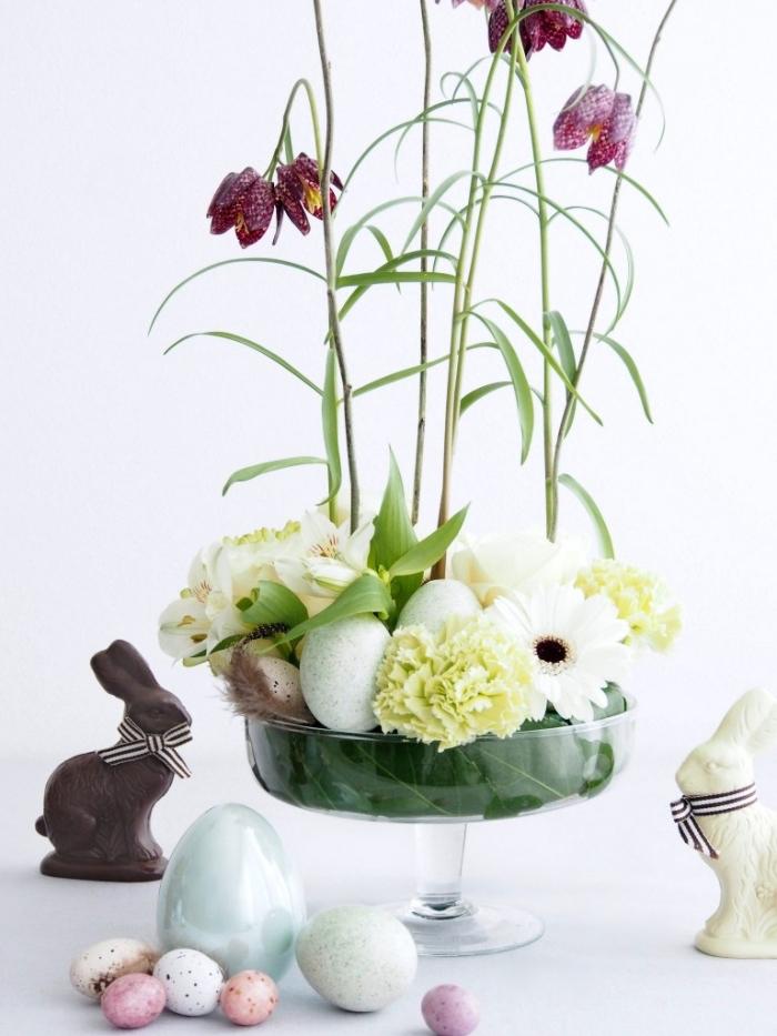 frühling deko tisch gesteck, glasvase dekoriert mit blumen und eiern, schokoladenhase