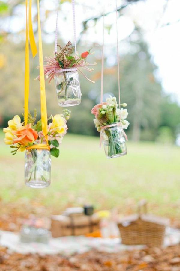 hängende-gläser-mit-blumen-als-dekoration-für-die-gartenparty