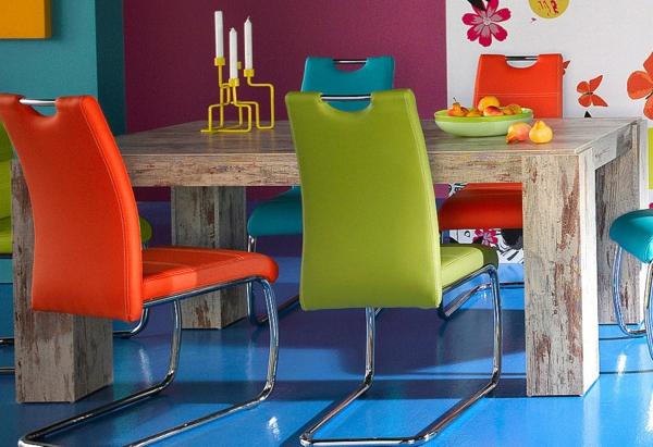 hölzerner-esstisch-im-vintage-stil-und-bunte-stühle