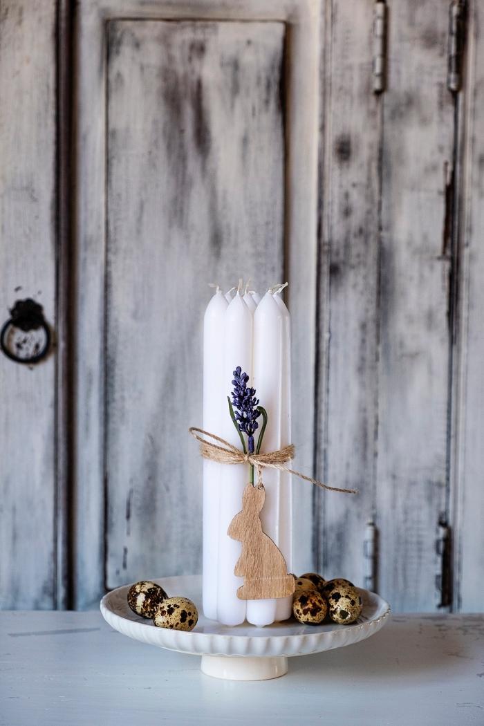 schöne tischdeko zum ostern, weiße kerzen dekoriert mit lavendel, leinen und holzhase