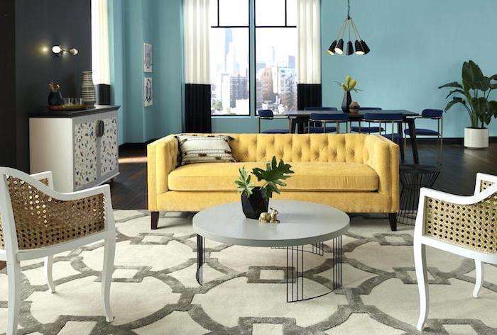 Wohnzimmer in Pastellfarben, gelbes Sofa, runder Couchtisch, Wandfarbe Türkis, Wand in Schwarz