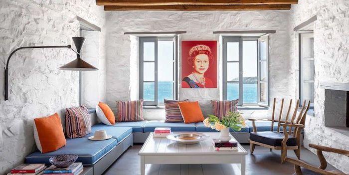 Wohnzimmer in Greek Wohnstil, grobe Wände in Weiß, Queen Porträt, blaues Sofa mit bunten Kissen, viereckiger weißer Couchtisch