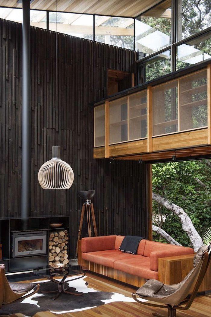 Wohnzimmer mit Outdoor Teil, rotes Sofa und Kamin, runder Kronleuchter, rundes Couchtisch, Holzboden