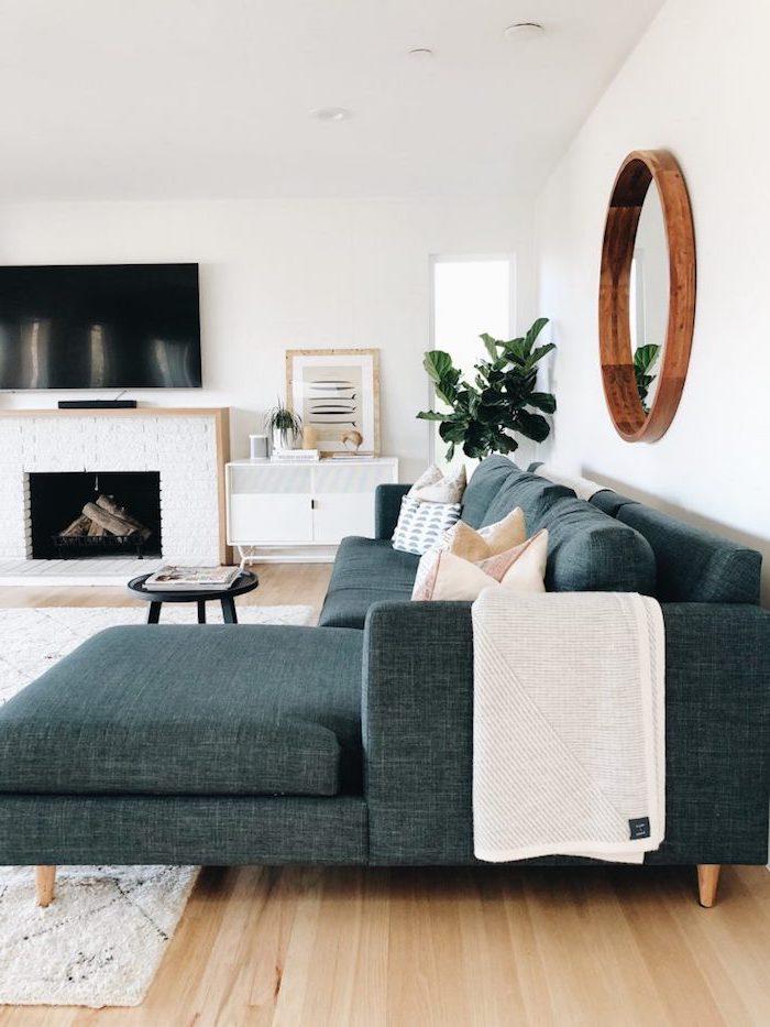 Wohnzimmer Einrichtung, Wandfarbe Weiß, runder Spiegel an Wand, blaues Sofa, Fernseher auf Kamin
