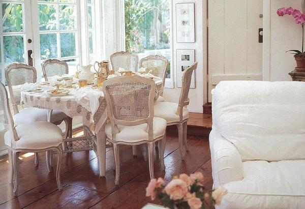 shabbystil - runder esstisch mit vielen stühlen neben der gläsernen wand