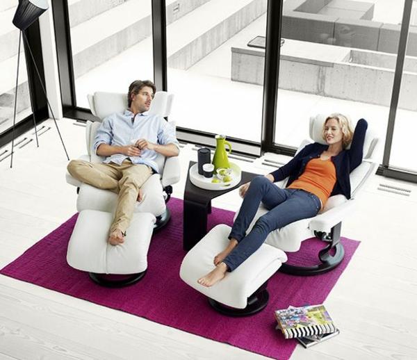 stressless-sessel-modelle-ein-mann-und-eine-frau-erholen-sich-imä-wohnzimmer-mit-gläsernen-wänden