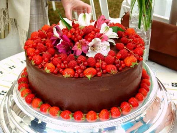 exotisches obst dekoration - leckere torte mit schokolade, obst und blumen darauf