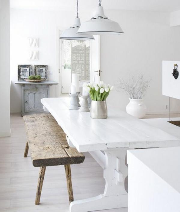 weißer-esstisch-im-vintage-stil-und-eine-hölzerne-sitzbank-daneben