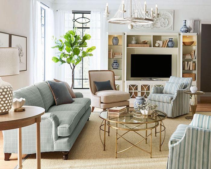 Wohnzimmer Einrichtung in hellen Pastellfarben, kariertes Sofa in Hellblau, gestreifte Sessel, rundes Couchtisch aus Glas und Metall