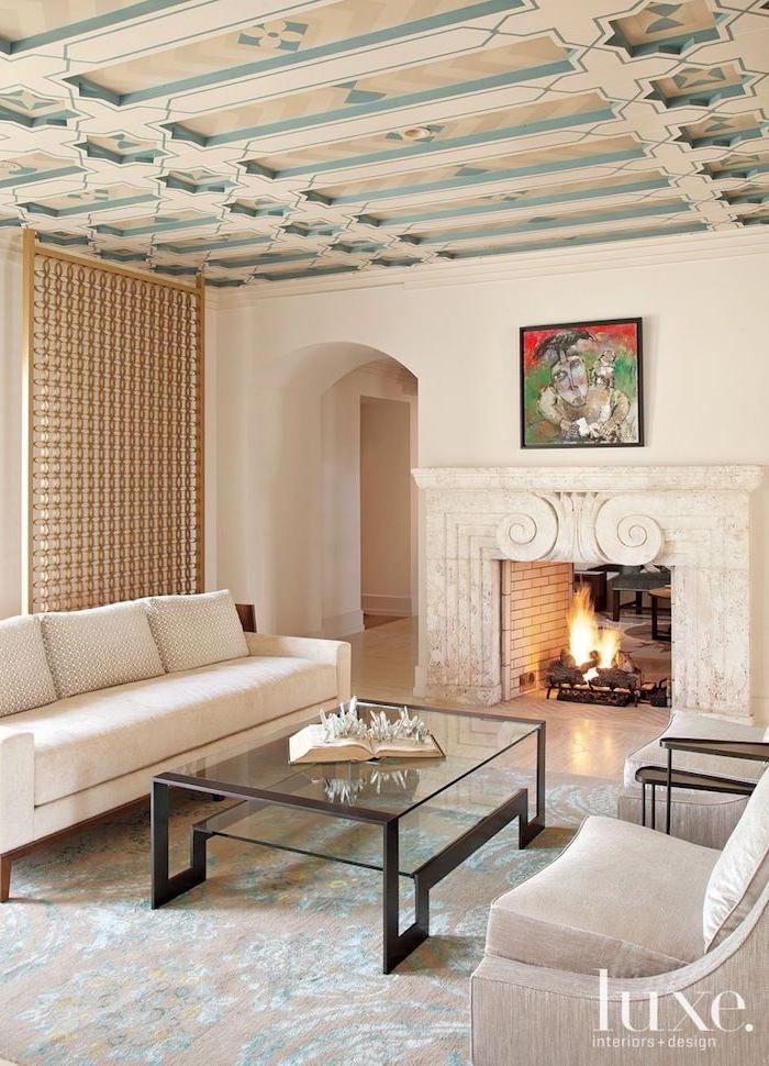 Wohnzimmer in Weiß und Hellblau, viereckiger Glastisch mit Metallkanten, abstraktes Gemälde über Kamin