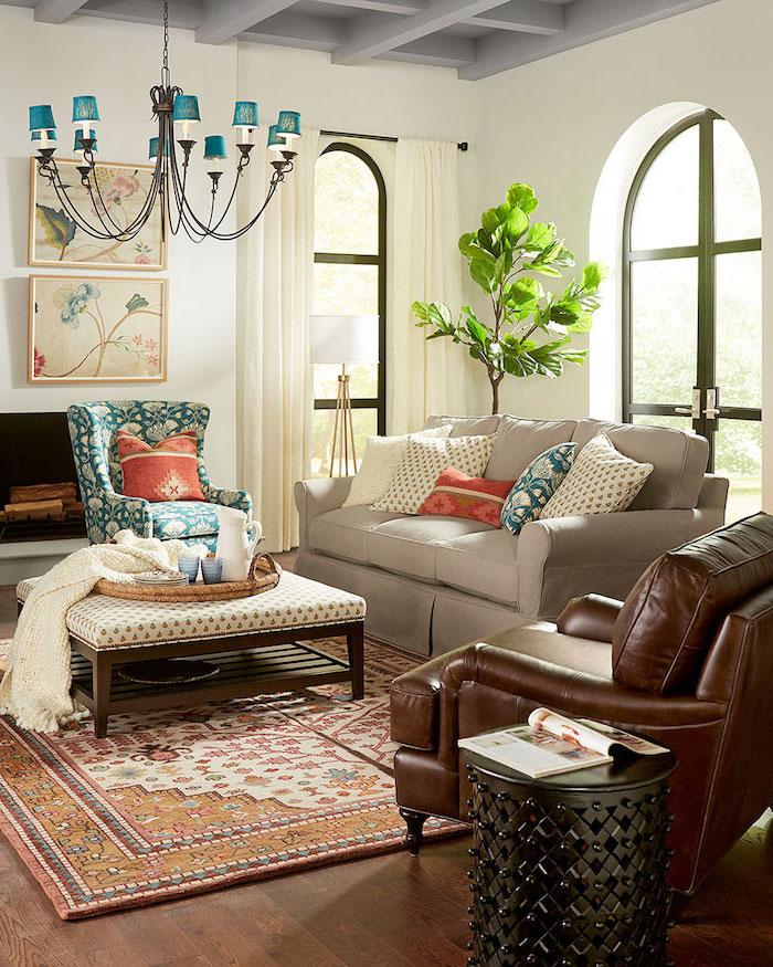 Wohnzimmer einrichten, brauner Ledersessel, weißes Sofa mit bunten Deko Kissen, Kanne und Becher auf Rattankorb, bunter Teppich