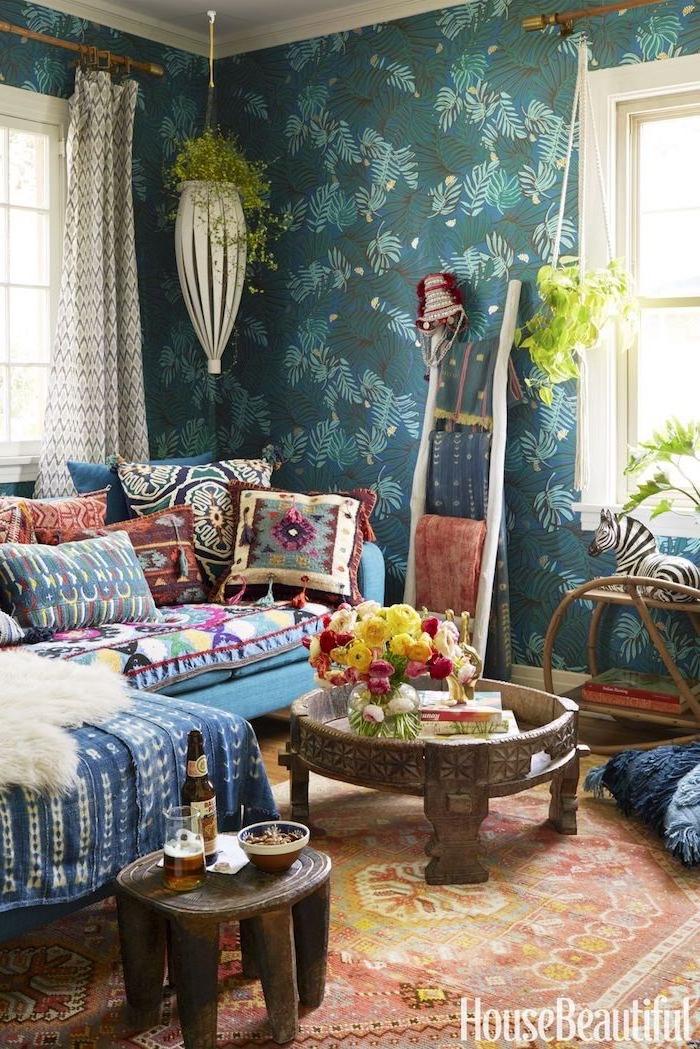 Wohnzimmer in Boho Stil, bunte Dekokissen und Decken in grellen Farben, niedriger Couchtisch und Hocker aus Holz, viele Grünpflanzen