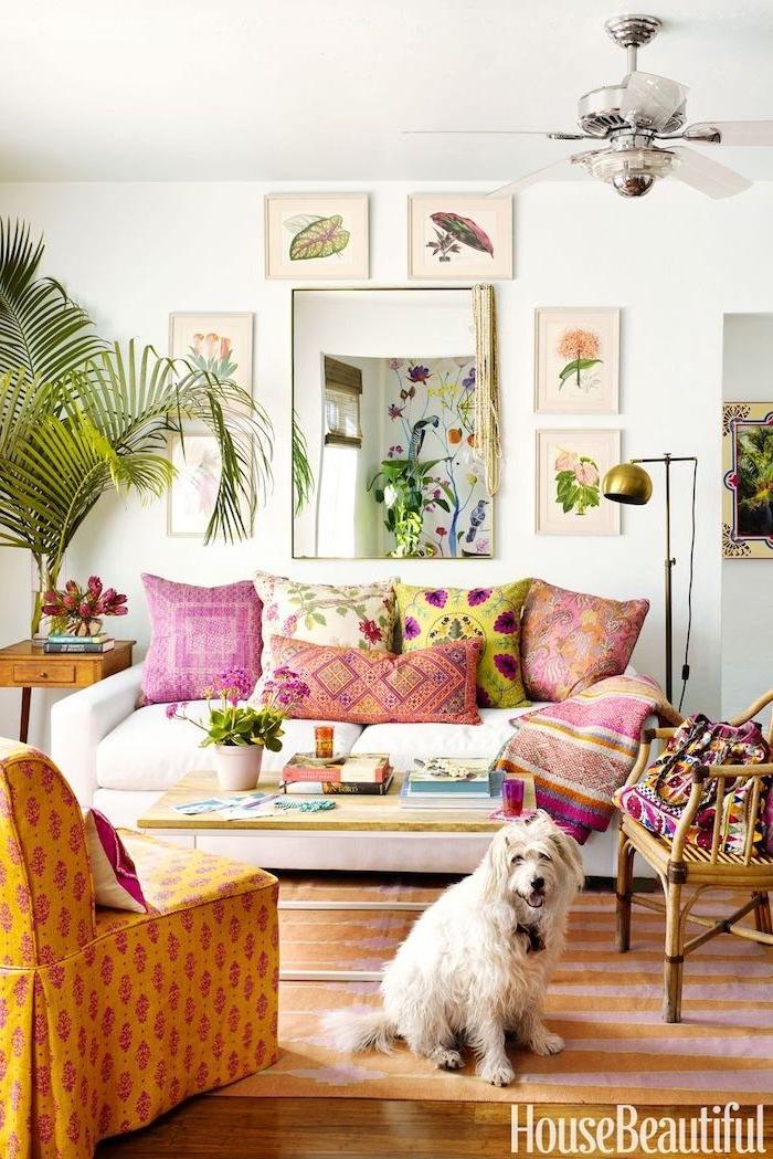 Boho Wohnzimmer einrichten, bunte Dekokissen auf weißem Sofa, Sessel in Orange, große Grünpflanze, Blumen Bilder, viereckiger Spiegel