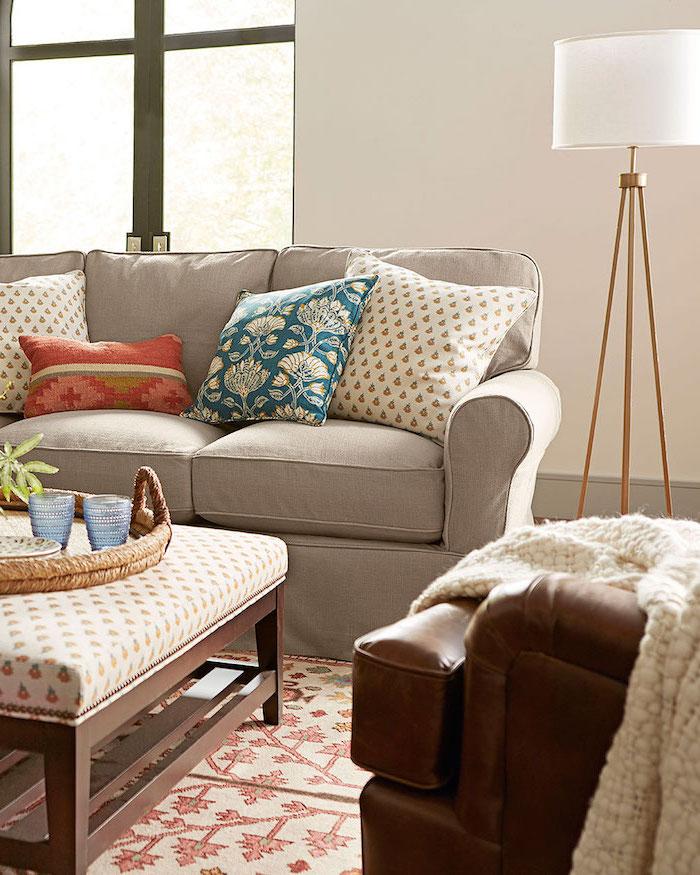Wohnzimmer einrichten, Sofa in Beige mit bunten Deko Kissen, brauner Ledersessel, weiße Stehlampe