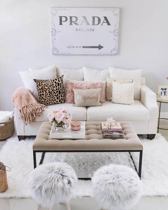 Wohnzimmer in hellen, zarten Farbnuancen, weißes Sofa, Kissen mit Leopardenprint, fluffige Hocker, Schild Milan Prada
