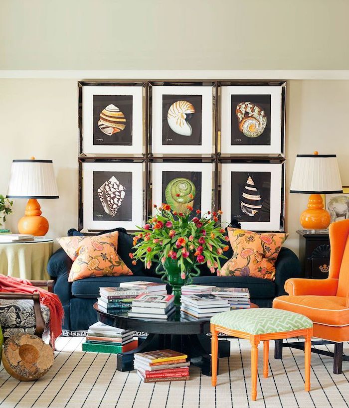 Wohnzimmer Einrichtung in grellen Farben, Muschel Bilder, Sessel und Deko Kissen in Orange, Bücher und Tulpenstrauß in Glasvase