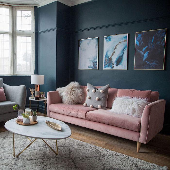 Wohnzimmer Einrichtung in Pastellfarben, rosafarbenes Sofa mit flauschigen Deko Kissen, Wandfarbe Dunkelblau, abstrakte Gemälde