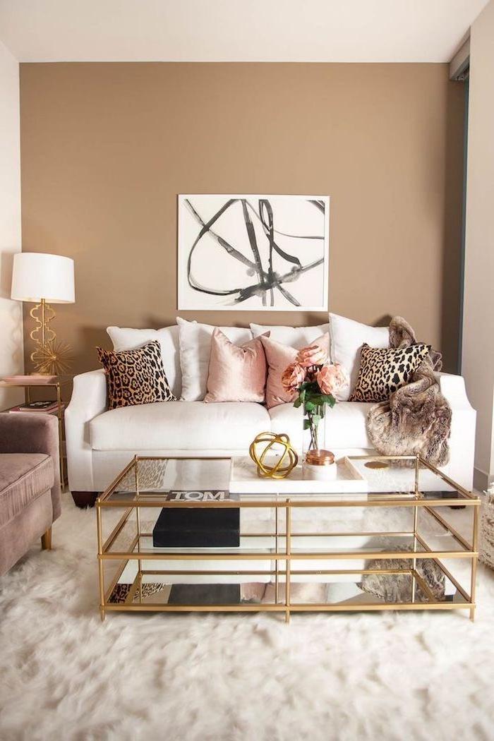 Wohnzimmer in Beige, weißes Sofa, Deko Kissen in Rosa und mit Leopardenprint, Glastisch mit goldenen Kanten