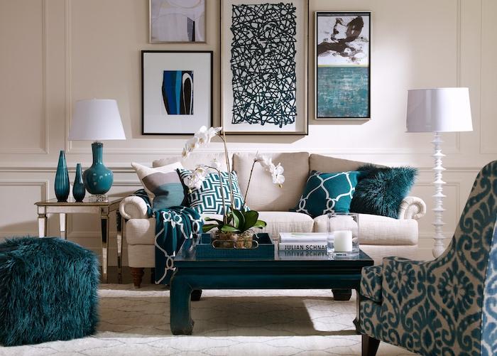 Wohnzimmer Einrichtung Ideen, weißes Sofa, dunkelblauer viereckiger Couchtisch, blaue Deko Kissen und Hocker, Sessel mit Blumenmuster