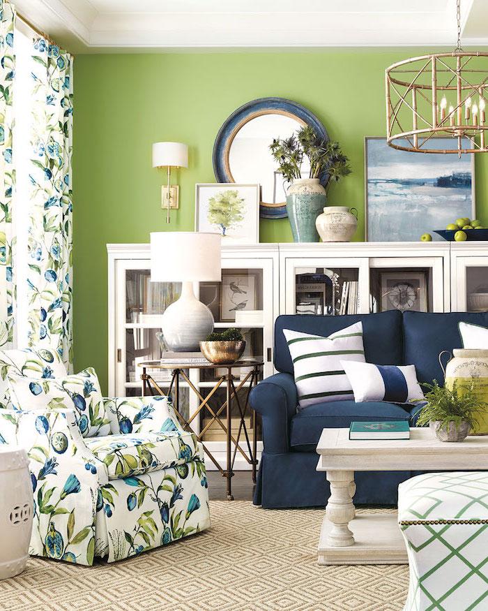 Wohnzimmer in frischen Farben, Wandfarbe Hellgrün, Sessel und Gardinen mit Pflaumen Muster, weiße Schränke und Couchtisch