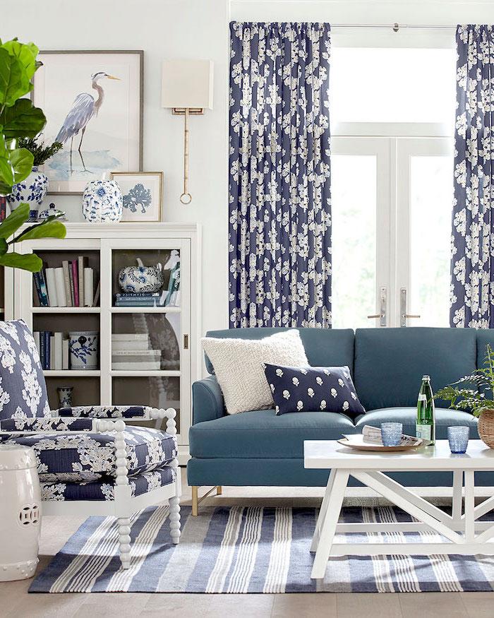 Wohnzimmer in Strand Stil, Einrichtung in Dunkelblau und Weiß, gestreifter Teppich, weißer viereckiger Holztisch