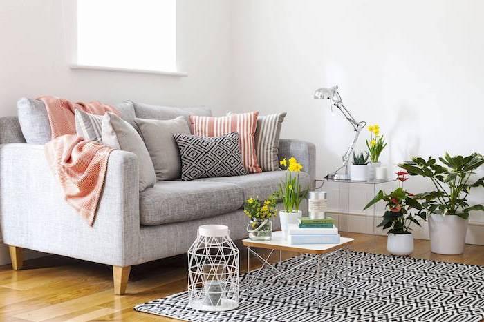 Wohnzimmer in Skandinavischer Stil einrichten, Wandfarbe Weiß, graues Sofa, viele Pflanzen, Narzissen in kleinen Blumentöpfen