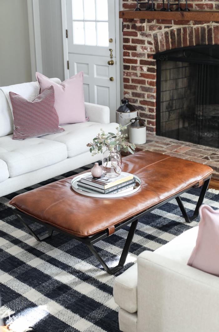 Wohnzimmer in Landhausstil einrichten, Couchtisch mit Lederoberfläche, weißes Sofa mit rosafarbenen Dekokissen