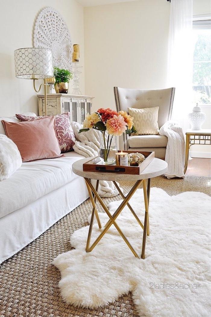 Landhaus Einrichtung in hellen zarten Farben, weiße Möbel, rosafarbene Deko Kissen, Pelz am Boden
