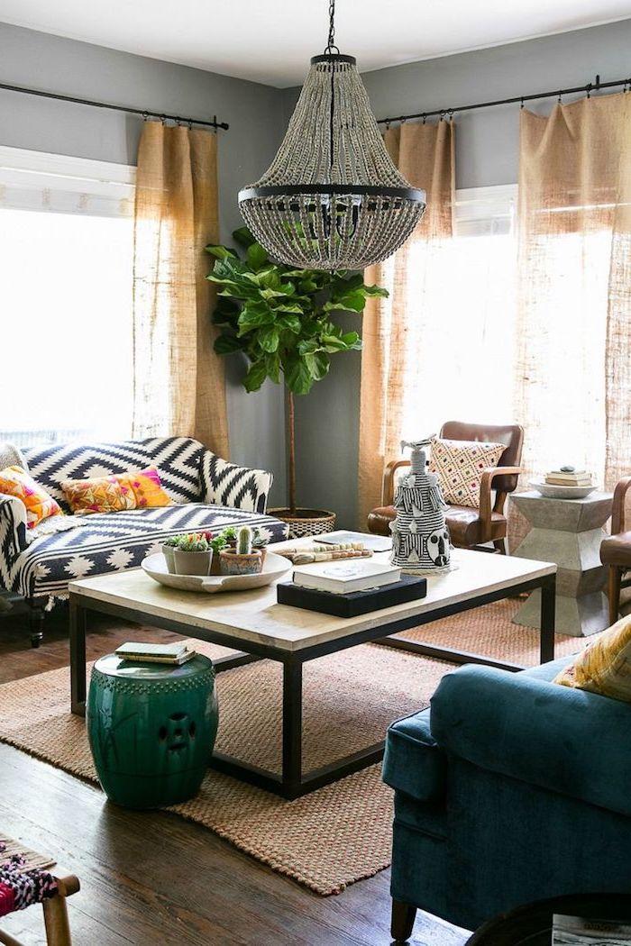 Wohnzimmer traditionell einrichten, Couchtisch mit Holzoptik, großer Kronleuchter, Sofa in Schwarz und Weiß, blauer Sessel