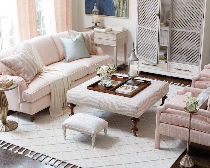 Wohnzimmer in zarten Pastellfarben, Sofa und Sessel in Zartrosa, weißer Teppich, Laterne mit weißer Kerze