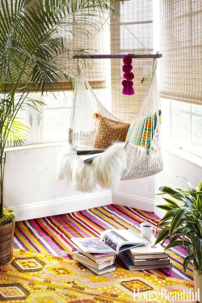 Boho Einrichtung Ideen, Hängematte im Wohnzimmer, bunte Teppiche, Bücher und Tasse Kaffee am Boden, große Grünpflanzen