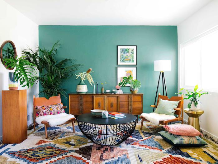 Vintage Wohnzimmer Einrichtung, eine Wand in Grün, Retro Möble aus Holz, bunter Teppich, runder Couchtisch, große Grünpflanzen
