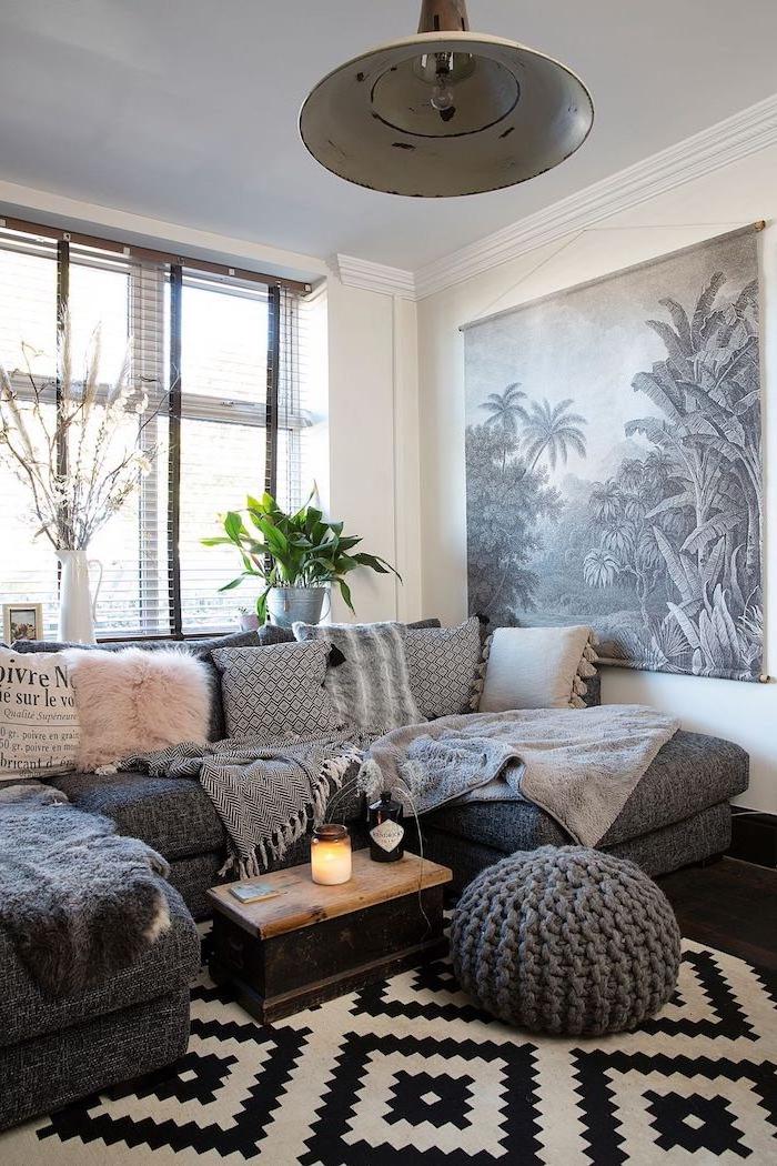 Boho Wohnzimmer Ideen, graues Sofa mit kleinen Deko Kissen, gestrickter Hocker, Teppich in Schwarz und Weiß