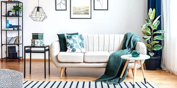 Wohnzimmer minimalistisch einrichten, weißes Sofa mit grünen Deko Kissen und Decke, Regale aus Metall