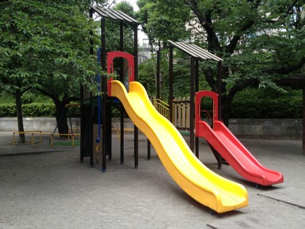 zwei-rutschen-in-rot-und-gelb-am-spielplatz
