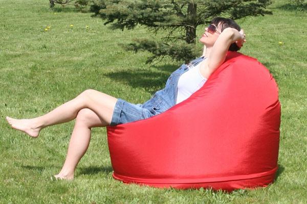 eine-frau-erholt-sich-auf-einem-roten-sitzsack-outdoor