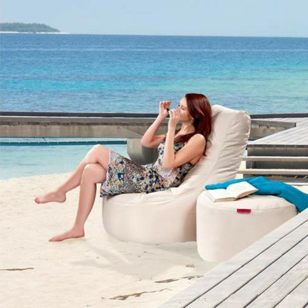 eine-frau-erholt-sich-auf-einem-weißen-sitzsack-outdoor-am-strand