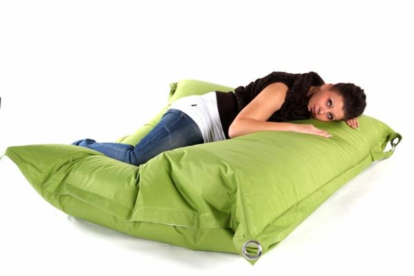 eine-frau-liegt-auf-einem-sitzsack-outdoor-in-grüner-farbe