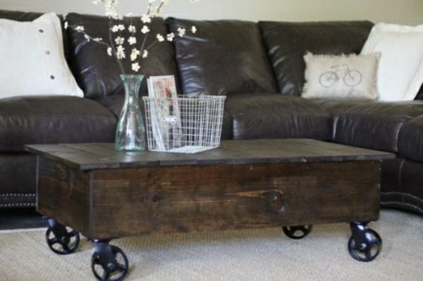 kreativ-gestalteter-und-sehr-auffälliger-tisch-auf-rollen-braunes-sofa-aus-leder-daneben